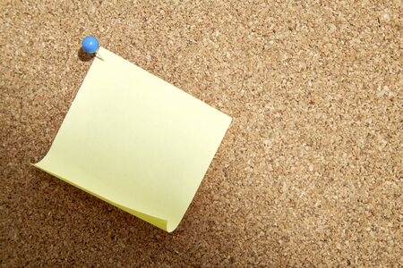 corkboard: Blank yellow paper note with blue pin on corkboard Stock Photo