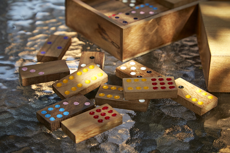 topple: Wood domino game on glass table, daylight Stock Photo