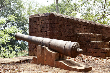 armaments: Ancient cannon and old wall in Thailand.