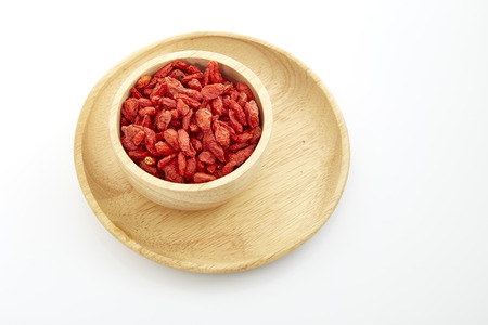 wolfberry: Dried Tibetan goji berries (wolfberry) in wooden bowl isolated on white background.