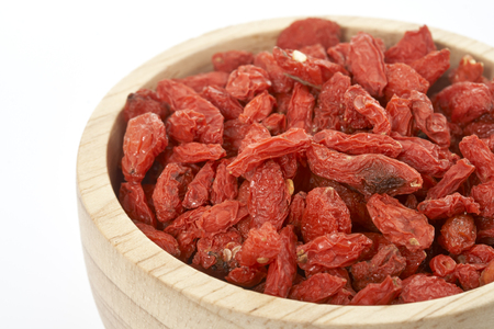 goji berry in wooden cup on white background.