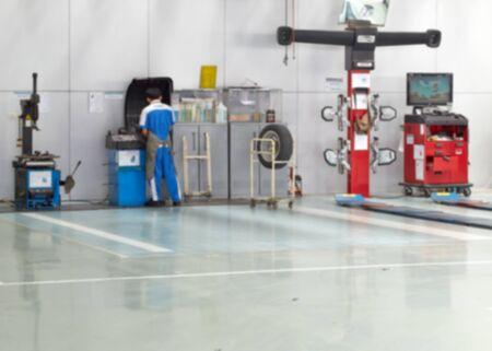 adjusting: auto repair service station blurred background, Adjusting Wheel Stock Photo