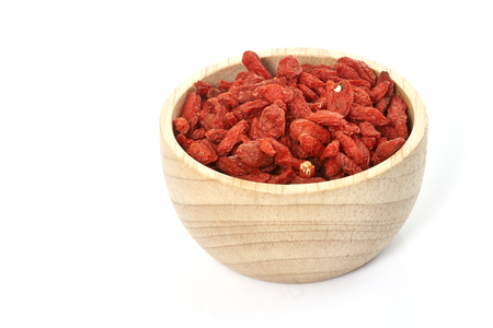 lycii: goji berry in wooden cup on white background.