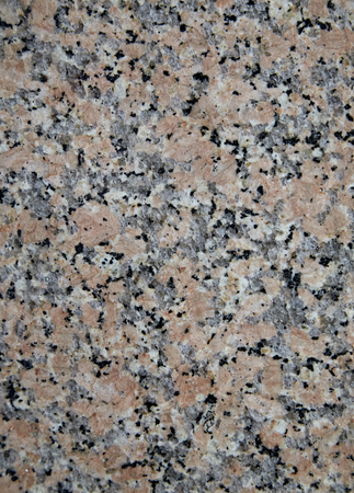 fireplaces: Granite Blacksmith. Natural stone texture with pink-red color with a lot of black inclusions. The surface of the building material for finishing floors and walls, fireplaces and staircases