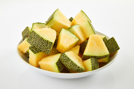 Fresh melon slices on white plate, top viwe melon