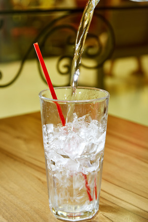 red tube: highball glass with ice and a red tube on the wooden bar