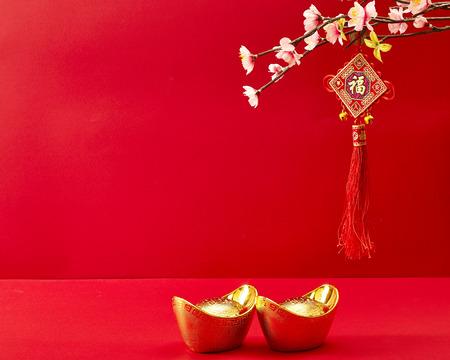 Decoración de año nuevo chino sobre un fondo rojo Flores de buena fortuna y terrón de oro. Foto de archivo - 69773087
