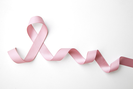 Pink awareness ribbon with trail on white background 免版税图像