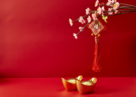 Chinese New Year decoration on a red background  Flowers of good fortune and lump of gold.