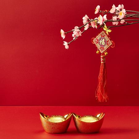 Decorazione cinese di nuovo anno su uno sfondo rosso Fiori di buona fortuna e grumo d'oro. Archivio Fotografico