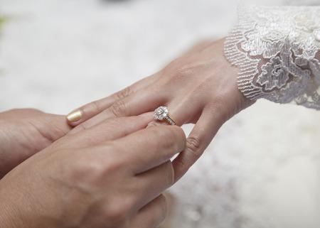hand wear: Male hand wear diamond ring in to female finger Stock Photo