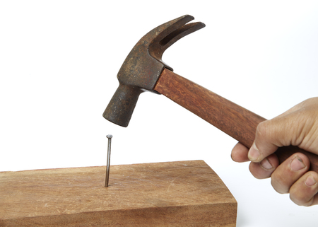 Hammer pounding a nail in a wooden board Stock Photo