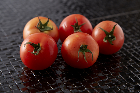 Close up of Fresh red tomatoes on black tile floor