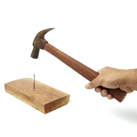 claw hammer: Hammer pounding a nail in a wooden board Stock Photo
