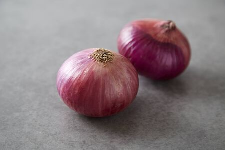Red onions on Gray granite slab background. Organic food. Vegetarian concept. Stock Photo