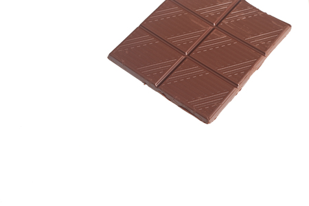 carbohydrates: Broken chocolate bar left position isolated on white table
