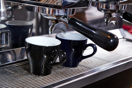 crema: Close-up of espresso pouring from coffee machine