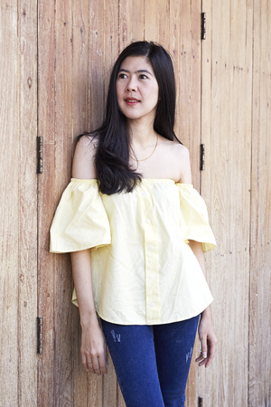 gir: Portrait Asian young modern gir with long black hair with modern dress, yellow shirt, jeans looks bright behind old wooden door