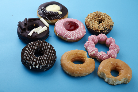 Colorful sweet donuts on the blue background , top View