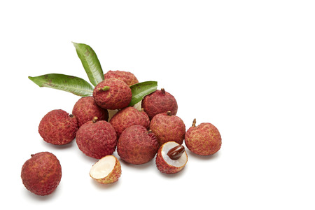Sweet lychees fruits with leaves close up on white background Stock Photo