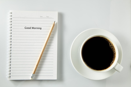 todo: White cup of coffee morning on wooden table with notebook,soft focus photo, good morning concept Stock Photo