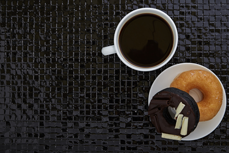 junk: Fresh donuts with hot black coffee placed on a black ceramic tile desk Stock Photo