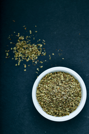 spice: Dried oregano herbs in white bowl on black background