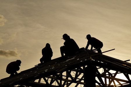 Contractor in Silhouette working on a Roof Top with  Sky in background