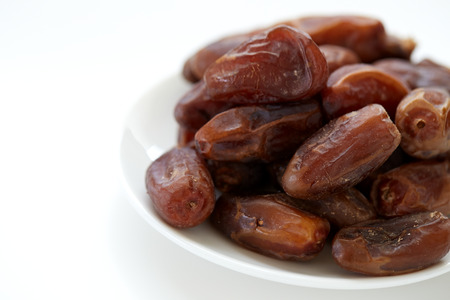 bowl of pitted dates isolated on white background, top view