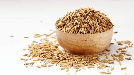 Paddy seeds in wooden bowl on white background