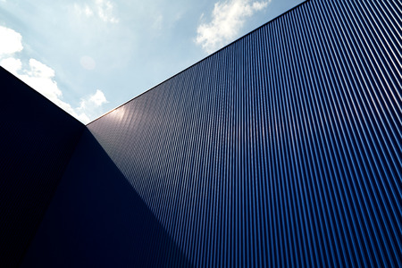 Metal sheet wall panels and roofs against clear blue sky