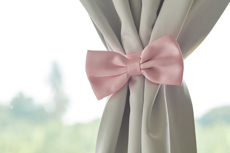 interior desing: Pink bow tie beautiful modern grey curtains in living room Stock Photo
