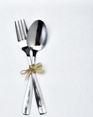 Fork and spoon with gold ribbon on white background