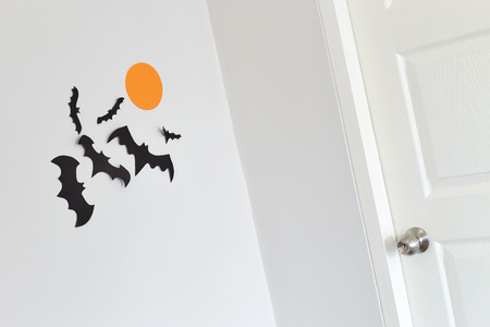 halloween decoration and scary concept - black paper bats flying with orange paper moon wall white background Stock Photo