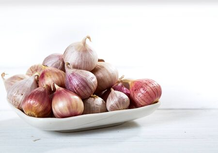 spiciness: Fresh garlics in ceramic bowl on wooden white table background Stock Photo