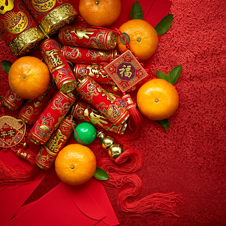 Chinese coins of luck and chinese firecrackers or chinese knot and Chinese gold ingots and Traditional chinese knot  (Foreign text means blessing) and Red envelopes and decoration with Fresh oranges on Red Paper background Фото со стока
