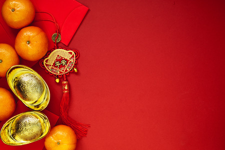 Chinese coins of luck or chinese knot and Chinese gold ingots and Traditional chinese knot  (Foreign text means blessing) and Red envelopes and decoration with Fresh oranges on Red Paper background Banco de Imagens - 89269062