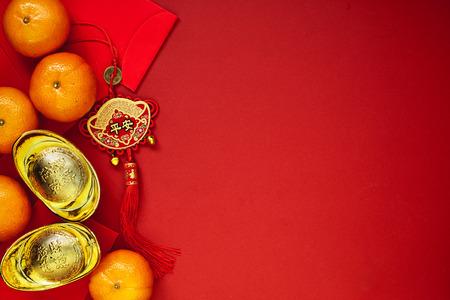 Monedas chinas de suerte o nudo chino y lingotes de oro chino y nudo chino tradicional (texto extranjero significa bendición) y sobres rojos y decoración con naranjas frescas sobre fondo de papel rojo Foto de archivo - 89269062