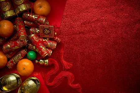 Chinese coins or Chinese knot of luck and chinese firecrackers  and Chinese gold ingots and Traditional chinese knot  (Foreign text means blessing) and Red envelopes and decoration with Fresh oranges on Red Paper background