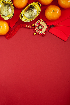 Chinese coins of luck or chinese knot and Chinese gold ingots and Traditional chinese knot  (Foreign text means blessing) and Red envelopes and decoration with Fresh oranges on Red Paper background Imagens - 89325230