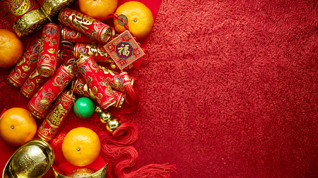 Chinese coins luck and firecrackers or chinese knot and Chinese gold ingots and Traditional (Foreign text means lucky blessing) and red envelopes and decoration with fresh oranges on red paper background