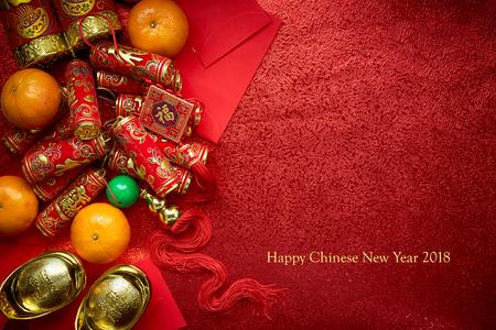 Chinese munten of Chinese knoop van geluk en Chinees vuurwerk en Chinese goudstaven en traditionele Chinese knoop (buitenlandse tekst betekent zegening) en rode enveloppen en decoratie met verse sinaasappelen op rode achtergrond papier Stockfoto