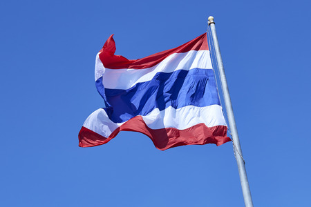 State national flag of Thailand waving on blue sky background.