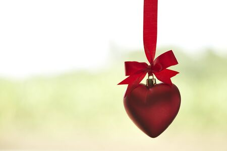 red hearts on ribbon green background, minimal concept