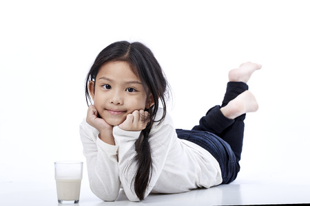 Happy asian girl eating a milk on the floor,education concept