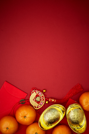 Chinese coins of luck or chinese knot and Chinese gold ingots and Traditional chinese knot  (Foreign text means blessing) and Red envelopes and decoration with Fresh oranges on Red Paper background