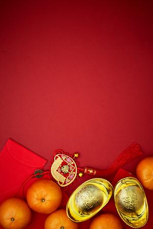 Monete cinesi di fortuna o nodo cinese e lingotti d'oro cinese e nodo cinese tradizionale (testo straniero significa benedizione) e buste rosse e decorazione con arance fresche su sfondo di carta rossa Archivio Fotografico - 93322519