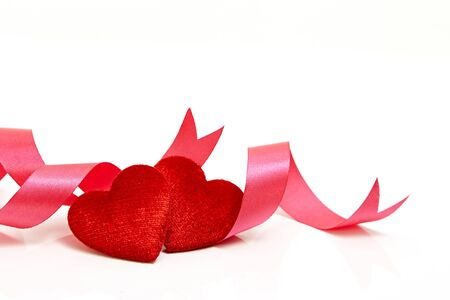 Two red hearts with pink ribbon isolated on white background