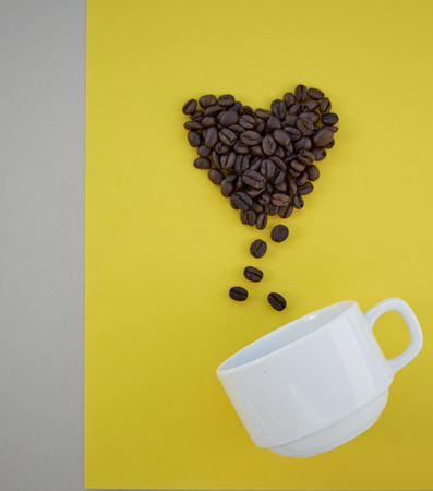 Coffee beans in shape of heart  with white cup on yellow background. valentines concept.