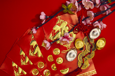 chinese new year festival decorations plum flowers wthi Firecrackers, envelopes, lucky Chinese five gold medals on red with copy space (Foreign text means lucky blessing)